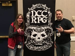 Andrea and Blair point to a Dungeon Crawl Classics banner.