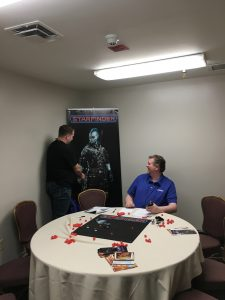 Blair pretending to shake hands with a Starfinder character on a poster, while Jason Bulmahn laughs.